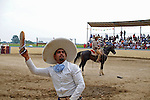 A participant in the Mexican rodeo Charros del Norte throws back the shoes of members of the audience who threw them into the rodeo arena in a gesture of approval in Lowell, Indiana on July 27, 2008.