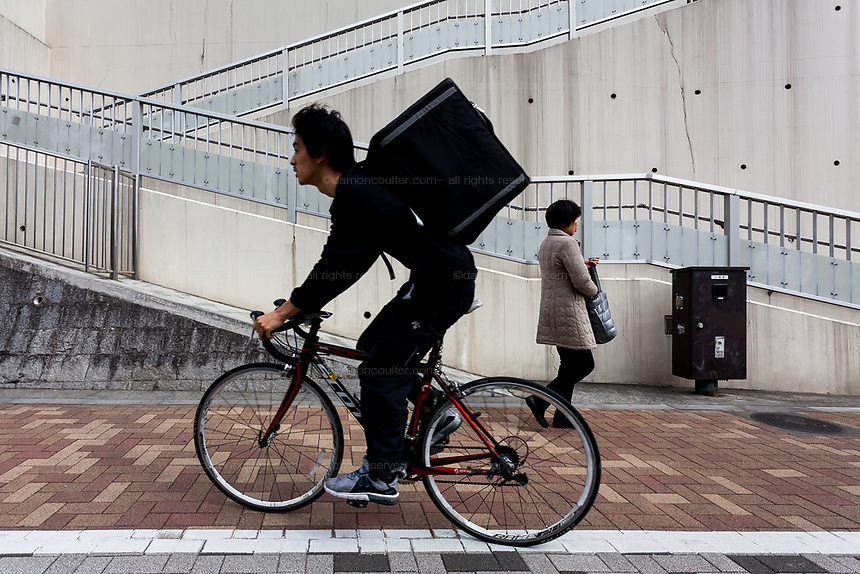 A Uber Eats deliver bicycle rides past a woman on a sidewalk in Shinjuku, Tokyo, Japan. Friday March 22nd 2019