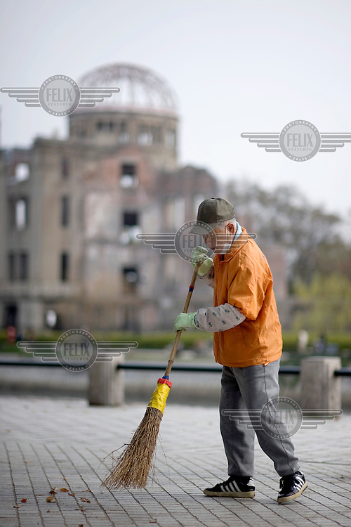 A worker sweeps leaves from a path in front of the Hiroshima Peace Memorial (Genbaku Dome). It was the only building left standing at the hypocentre of the bomb blast following the detonation of the 'Little Boy' atomic bomb, dropped on 6 August 1945. /Felix Features