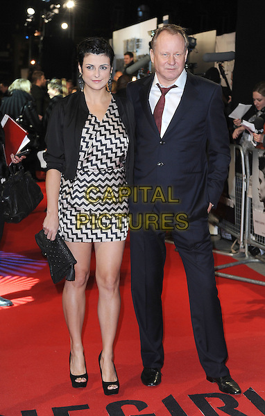 Megan Everett and Stellan Skarsgard.'The Girl With The Dragon Tattoo' World film Premiere, Odeon Leicester Square, London, England..12th December 2011.full length white shirt black suit hand in pocket print dress married husband wife .CAP/BEL.©Tom Belcher/Capital Pictures.