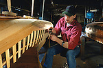 Boatbuilder working on the planking of a wood and canvas canoe, Old Town, Maine, USA