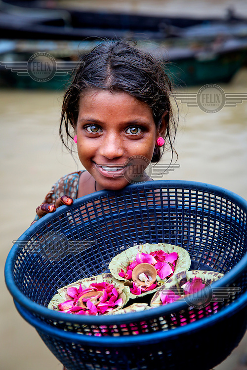 A girl, with striking grey/green eyes, sells candles in leaf holders to devotees on the banks of the Ganges River.