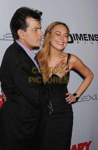 "Charlie Sheen, Lindsay Lohan.arriving at the Los Angeles Premiere of ""Scary Movie 5"" at ArcLight Cinemas Cinerama Dome in Hollywood, California, USA, .April 11th 2013. .half length  black cleavage plaits hair braids  tanned fake tan gold straps necklace cross dress hand on hip arm around funny smiling suit purple shirt tie .CAP/ROT/TM.©TM/Roth Stock/Capital Pictures"