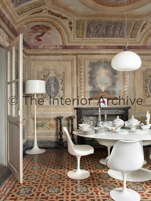 In a dining room in the Palazzo Orlandi,  a modern white Eero Saarinen Tulip table and chairs and a floor lamp contrast with, yet compliment, the traditional richly decorated walls by Luigi Catani, a leading 18th century fresco painter.