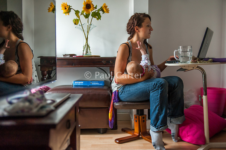 A young graphic designer breastfeeds her baby whilst working at her computer at home. They are reflected in the television.<br /> <br /> 10/09/12<br /> Berkshire, England, UK