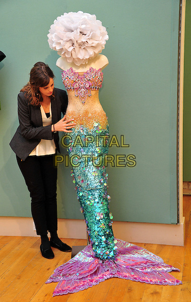 An Auction House Member of Staff pictured with a mermaid costume previously worn by Katy Perry..Est: £2,000-3,000..Christie's London Pop Culture photocall.  Collection of important memorabilia from the past century to auction on November 29 at Christie's London.  Highlights include items from the recent James Bond film Skyfall and original Jean-Paul Gaultier clothing worn by Madonna. Christie's London, London, United Kingdom, November 23rd 2012..full length pink green turquoise paillettes sequined sequin tail hat bra .CAP/BF.©Bob Fidgeon/Capital Pictures.