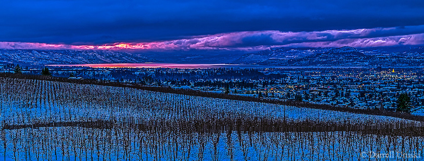 Fine Art Winter Scenic during the late fall season of a spectacular sunset on Okanagan Lake. A cherry orchard the distant lights of the city of Kelowna BC, Canada harmonize with the drama from the sunset on the lake.