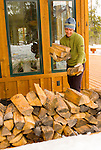 A young woman collects firewood from the stack at her home in Wilson, Wyoming.