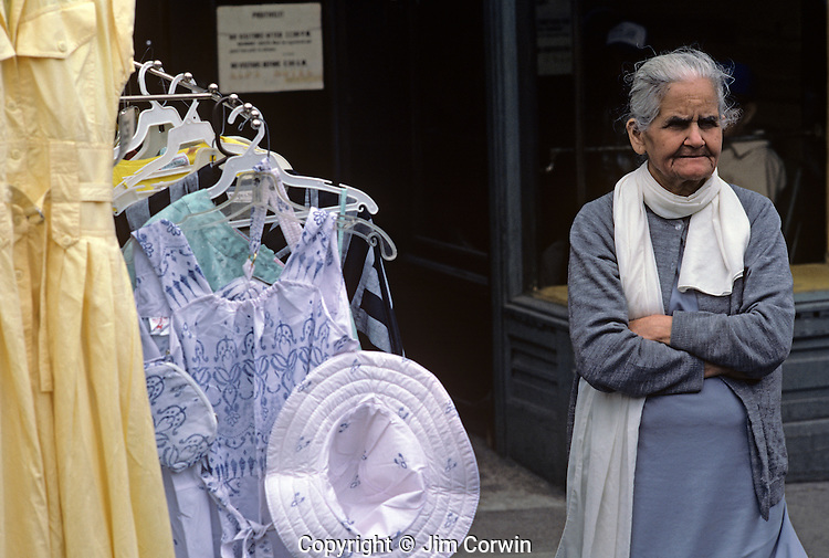 Woman standing in front of her shop at street fair selling clothes with a serious expression on her face