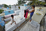 "In the capital of the Philippines, Aramay Calma (right) hangs laundry over tombs in the Manila North Cemetery, where she lives, as a small child jumps from one tomb to another. Hundreds of poor families live here, dwelling in and between the tombs and mausoleums of the city's wealthy. They are often discriminated against, and many of their children don't go to school because they're too hungry to study and they're often called ""vampires"" by their classmates. With support from United Methodist Women, KKFI provides classroom education and meals to kids from the cemetery at a nearby United Methodist Church."