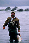 Fisherman standing in water holding salmon caught while fishing, Shelter Cove, Humboldt County, CALIFORNIA