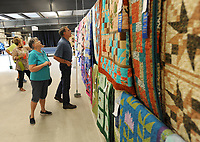 NWA Democrat-Gazette/ANDY SHUPE<br /> Joyce and Larry Faulkenbury of Rogers check out quilts on display Thursday, Aug. 10, 2017, at the Benton County Fair. Joyce entered nine quilts in this year's fair and was seeing what other entrants' work looked like.