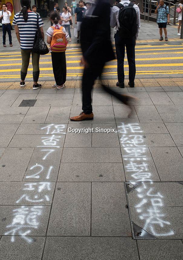 """Graffiti is sprayed on the streets in Central, Hong Kong by protestors. The graffiti reads """"Hong Kong police protect gangs (triads) but not the public"""".  Hong Kong has undergone 9 weeks of protests that began with the introduction of an extradition bill allowing criminals to be deported to the legal system in Mainland China but has grown wider into a pro-democracy movement."""