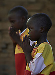 Children pray during Catholic Mass in Gidel, a village in the Nuba Mountains of Sudan. The area is controlled by the Sudan People's Liberation Movement-North, and frequently attacked by the military of Sudan.