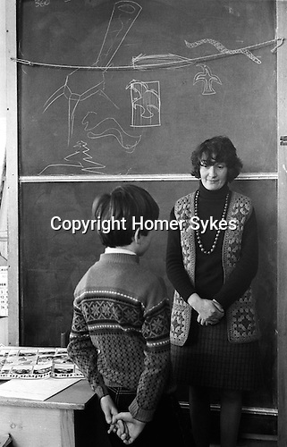 Junior school schoolmistress telling off a young schoolboy who has been brought to the front of the class for misbehaving. Carloway, Isle of Lewis,  Shetlands, Outer Hebrides Scotland 1974. She is wearing a homemade crochet sleeveless jerkin, and a string of Popit beads, and he is wearing a factory made wool Fair Isle patterned jumper.