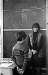 Junior school schoolmistress telling off a young schoolboy who has been brought to the front of the class for misbehaving.  Breasclete, Isle of Lewis and Harris,  Outer Hebrides Scotland 1974. She is wearing a homemade crochet sleeveless jerkin, and a string of Popit beads, and he is wearing a factory made wool Fair Isle patterned jumper.