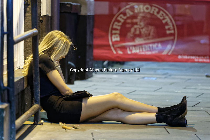 Pictured: A woman sits on the pavement. Friday 14 December 2018<br /> Re: Revellers in Wind Street, Swansea, Wales, UK.