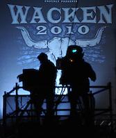 21st Wacken Open Air WOA  (5.8. - 7.8.2010) in Wacken (Germany , Schleswig-Holstein) - nearly 85000 metalheads celebrate their Mekka of metal - in picture: the wacken label on a huge flag mounted on the mainstage //  im Bild: das Symbol des Festivals , das Logo auf einem riesigen Banner / Fahne an den Hauptbühnen - Silhouette von Kameramännern . Foto: aif / Norman Rembarz
