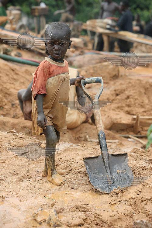 A young boy on a gold mining site in Obuasi. He is the child of one of many unemployed young people who have taken to working as illegal artisanal gold miners known as galamseys in Ghana.