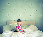 A young girl sat in bed alone looking thoughtful with green wallpaper