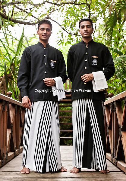 Two waiters stand on the wooden bridge at Saman Villas, Aturuwella, Bentota, Sri Lanka.