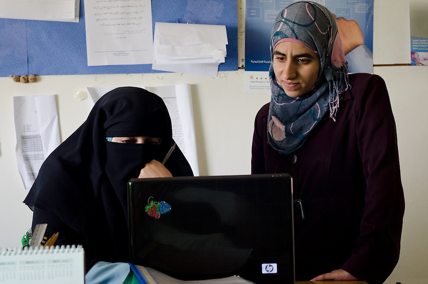 Abir Khawaldeh, manager of the community computer center in Qadisiyya, Jordan, helps Eslam Na'anah, an English Literature major studying at a university. Both are from formerly traditional bedouin families.