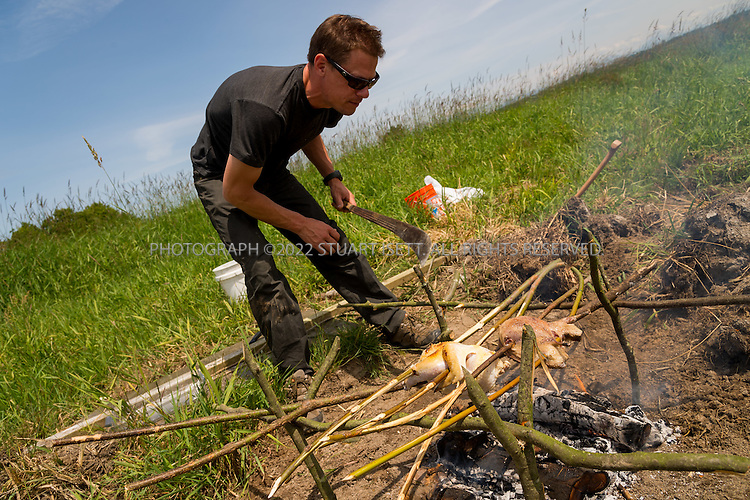 6/22/2015 &mdash; Everett, WA, USA<br /> <br /> Steven Rinella, an avid outdoorsman and hunter, prepares to cook both wild duck and domesticated chicken over an open wood fire in Everett, WASH. <br /> <br /> Here Rinella places the skewered duck  and chicken over the fire on a spit built duck with branches from nearby Alder branches.<br /> <br /> <br /> Photograph by Stuart Isett<br /> &copy;2015 Stuart Isett. All rights reserved.