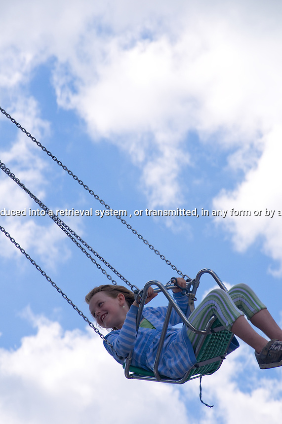 Young Girl having fun on swing ride at the amusement park