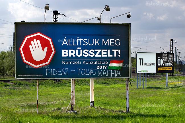 UNGARN, 04.2017, Budapest - X. Bezirk. &quot;Lasst uns Bruessel stoppen!&quot; Kampagne der Fidesz-Regierung gegen teils erfundene Massnahmen der EU. Es wird zu einer weiteren Propaganda-Volksbefragung &quot;Nationale Konsultation&quot; gerufen. &ndash;Viele Plakate werden umgestaltet: &quot;Fidesz=Diebesmafia&quot;. Hinten Anti-Regierungs-Plakat der rechtsradikalen Jobbik-Partei: &quot;IHR arbeitet, SIE stehlen.&quot; | &quot;Let's stop Brussels!&quot; Fidesz government campaign against the EU, based on alternative facts. They call for yet  another propaganda-referendum named &quot;national consultation&quot;. &ndash;Many billboards receive comments: &quot;Fidesz=mafia thieves&quot;. In the background the far-right Jobbik party's anti-government campaign reading &quot;YOU work, THEY steal.&quot;<br /> &copy; Martin Fejer/EST&amp;OST