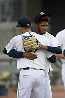 Starting pitcher Daison Acosta (18) of the Columbia Fireflies hugs pitching coach Josh Towers before a game against the Rome Braves on Saturday, August 17, 2019, at Segra Park in Columbia, South Carolina. Rome won, 4-0. (Tom Priddy/Four Seam Images)