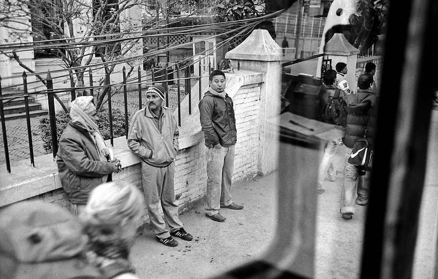 Nepalese men watch a foreign backpacker walk by on the streets of Kathmandu, Nepal, 2008. Photo: Ed Giles.