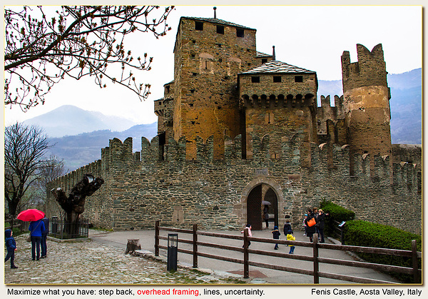 Italy, Aosta.  Maximize Your Image.<br /> Sometimes you have to make the best of a poor situation, like cloudy skies. Here I used overhead framing to diminish the gray sky and frame Fenis Castle. <br /> I stepped back and used a favorite personal icon, a fence, to create a strong diagonal line leading into the frame. Finally, I just watched the children playing and captured an active moment. And, the red umbrella does add a bit.