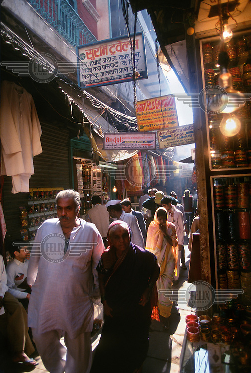 An elderly couple walk down a busy commercial street in the heart of the old holy city.