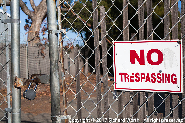 "A 'NO TRESPASSING"" sign on a chainlink gate with a padlock."