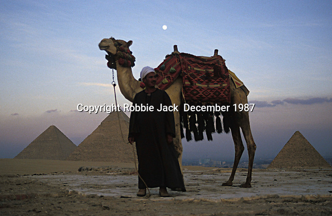 A man with a camel standing in front of the Pyramids of Giza which consist of the Great Pyramid of Giza also known as The Pyramid of Khufu, the somewhat smaller Pyramid of Khafre and the relatively modest sized Pyramid of Menkaure. Egyptologists believe that the Great Pyramid was built as a tomb for the Pharaoh Khufu around 2560 BC. It is the oldest of the seven wonders of the ancient world. At 481 feet high it remained the tallest man made structure in the world for over 3,800 years.