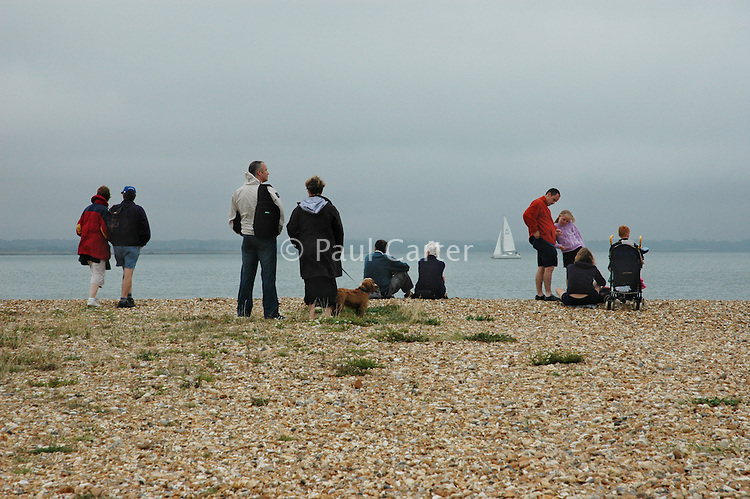 Families sitting on the shingle beach near Hurst Castle.  Hampshire.
