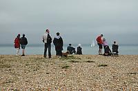 Families sitting on the shingle beach near Hurst Castle.  Hampshire.