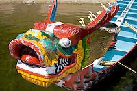 Fierce Asian dragon head on bow of racing boats moored at dock. Dragon Festival Lake Phalen Park St Paul Minnesota USA
