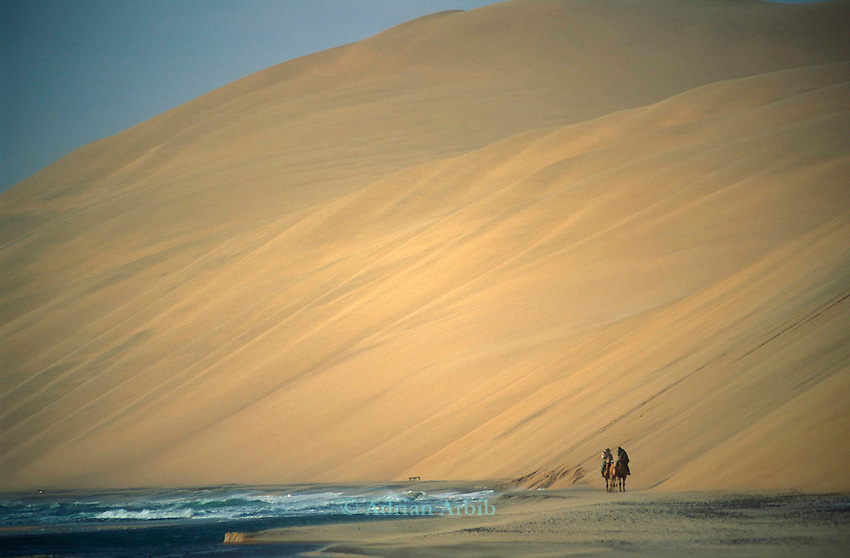 Tommy and  Benedict Allen  passing by the Langevaan a thousand foot high sand dune where the Namib Naukluft desert meets the Atlantic Ocean...Access is restricted due to Diamond mining activity by DeBeers.