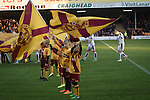 Motherwell 3 Dundee 1, 12/12/2015. Fir Park, Scottish Premiership. Mascots waving flags welcome the teams on to the pitch before Motherwell (in amber) play Dundee in a Scottish Premiership fixture at Fir Park. Formed in 1886, the  home side has played at Fir Park since 1895. Motherwell won the match by three goals to one, watched by a crowd of 3512 spectators. Photo by Colin McPherson.