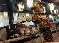 Samurai robot waiter serving food in the Hajime Restaurant, out-skirts of Bangkok, Thailand. Hajime is a Japanese restaurant in Thailand, has samurai style robot serving food to the diners and even do a dance session to entertain guests. This robot are made in Japan and costed about 86,600,000 yen (1,063,717USD). Customers order food from touch panel and Samurai robot will bring ordered food to their table.<br />15 Oct 2010