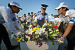 Workers remove a bin full of flowers as people leave floral offerings on August 6, 2015, at a memorial in Hiroshima, Japan, that commemorates the victims of the atomic bombing of the city by the United States in 1945.