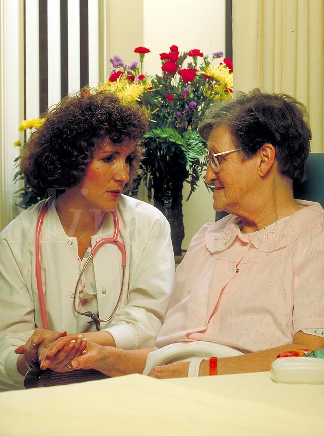 Nurse talks with elderly female patient in her hospital room.