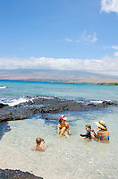 Two local moms talk and their children play in a warm tide pool at a beach in Puako, Big Island.