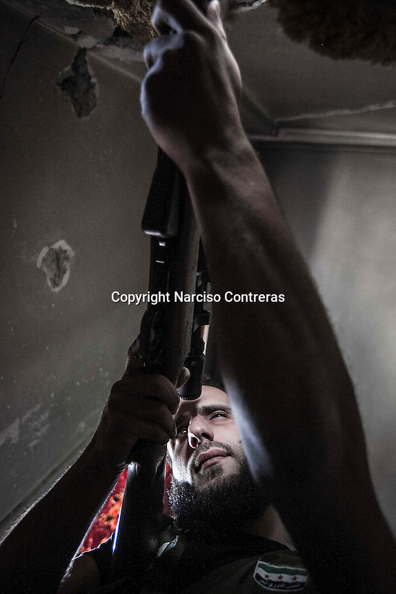 In this Sunday, Oct. 28, 2012 photo. A rebel fighter sniper keeps an eye over the enemy position as mortar explosions and gun machine shoots sound at the battlefield in Karmal Jabl neighborhood in Aleppo, the Syrian's largest city. (AP Photo/Narciso Contreras).
