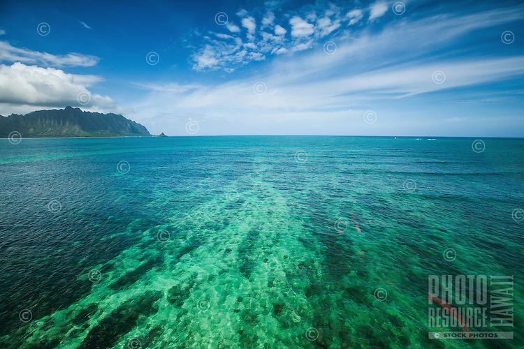 An aerial shot of green reefs past the Kane'ohe Bay Sandbar, with Chinaman's Hat in the far distance, O'ahu.