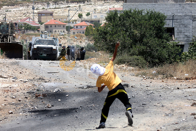 Palestinian protesters hurl a stones at Israeli soldiers during a demonstration against the expropriation of Palestinian land by Israel in the village of Kafr Qaddum, near the West Bank city of Nablus on June 1, 2012. Photo by Wagdi Eshtayah