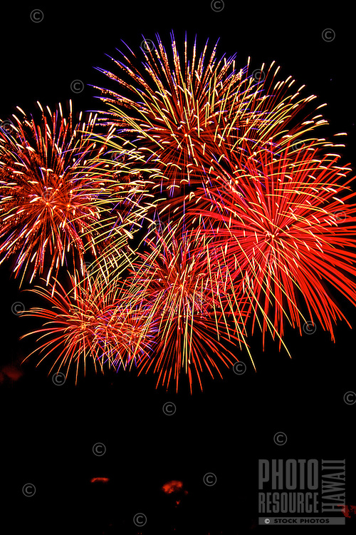 Spectacular brilliant red and yellow fireworks explode over Hilo Bay during the Fourth of July celebration.