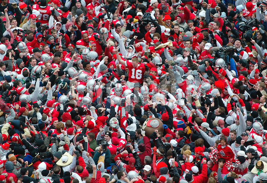 (KK OSUMI 03 23NOV02) Ohio State University fans flood onto the field and climb the south goal post after the Buckeyes clinched a spot at the BCS National Championship in Tempe Arizona. Craig Krenzel, # 16, is carried of the field. (Dispatch photo by Karl Kuntz) CAN YOU USE THIS AS A SIX COL. ACROSS THE FRONT OF THE PAPER