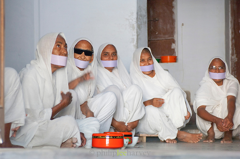 Jainist nuns sit together on a temple floor. Jainism is an ancient religion of India that prescribes a path of non-violence towards all living beings. The white cloth over their mouths is called Muhapatti to prevent saliva coming into contact with religous texts, and accidental inhaling of small insects. Bikaner, Rajasthan, India